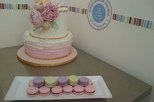 Bonnie Gordon School of Confectionary Arts, white floral cake and macaroons displayed on steel kitchen cart