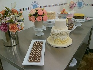 Bonnie Gordon School of Confectionary Arts, cakes, desserts and flower arrangements displayed on top of steel kitchen cart