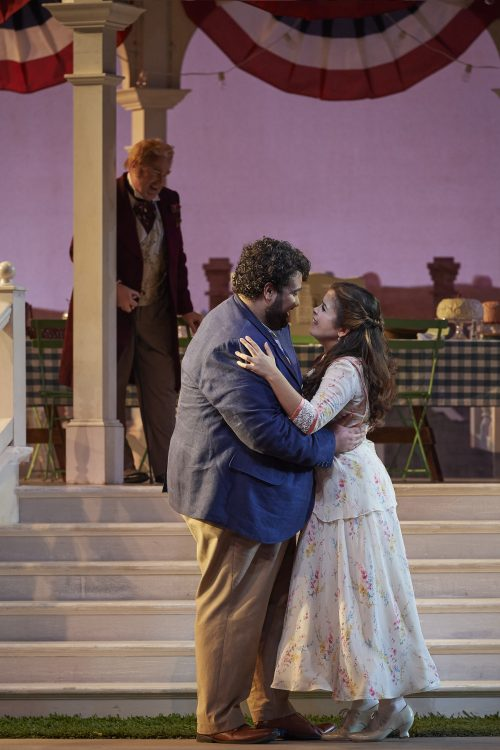Andrew Haji as Nemorino and Simone Osborne as Adina with Andrew Shore as Doctor Dulcamara (background) in the Canadian Opera Company's new production of The Elixir of Love, 2017. Conductor Yves Abel, director James Robinson, original costume designer Martin Pakledinaz, revival costume designer Amanda Seymour, set designer Allen Moyer, lighting designer Paul Palazzo,. Photo: Michael Cooper